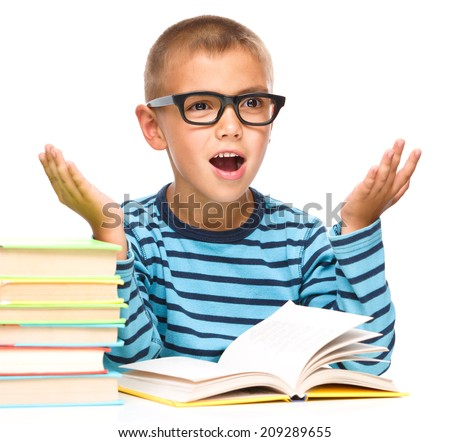 Cute little boy is reading a book while wearing glasses and explaining something gesturing with hands, isolated over white - stock photo