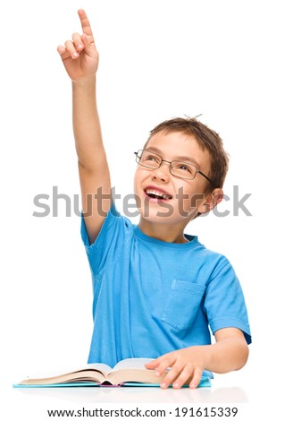 Cute little boy is reading a book while wearing glasses and pointing up using his index finger, isolated over white - stock photo