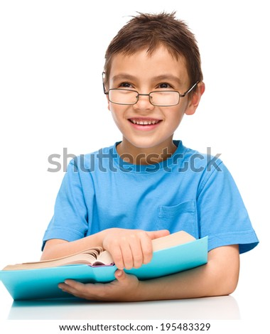 Cute little boy is reading a book while wearing glasses, isolated over white - stock photo
