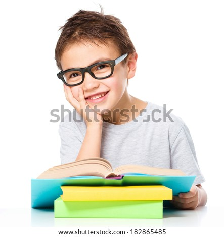 Cute little boy is reading a book while wearing glasses supporting his head with hand, isolated over white - stock photo