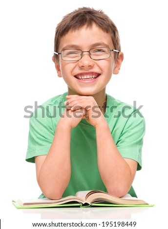 Cute little boy is reading a book while wearing glasses supporting his head with hands, isolated over white - stock photo