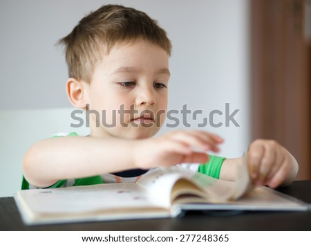 Cute little boy is reading book while sitting at table - stock photo