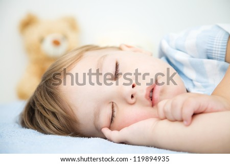 Cute little boy is sleeping in front of his teddy bear - stock photo