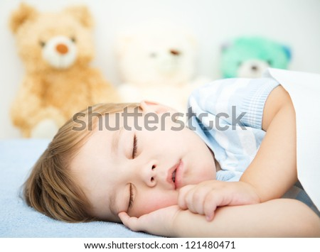 Cute little boy is sleeping in front of his teddy bears - stock photo