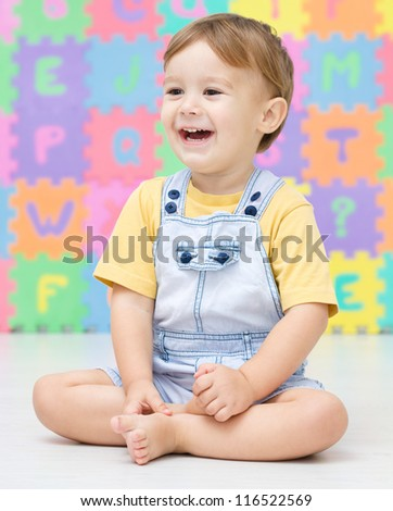 Cute little boy is smiling while sitting on the floor - stock photo