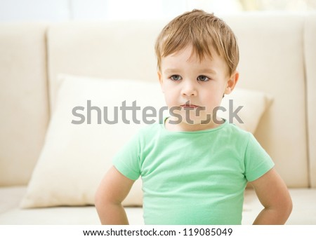 Cute little boy is standing in front of a sofa - stock photo