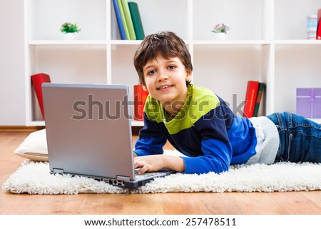 Cute little boy is using laptop at his home.Little boy using laptop - stock photo