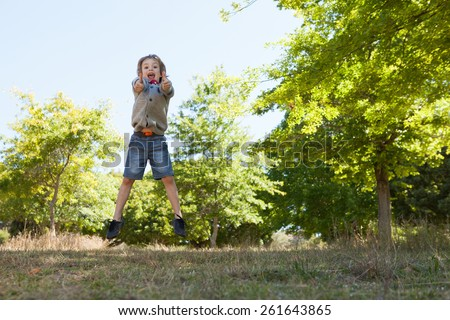 Cute little boy jumping in park on a sunny day - stock photo