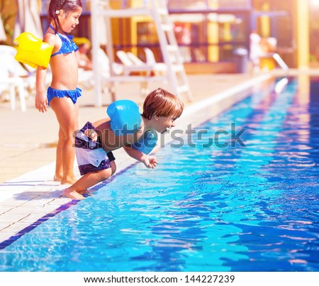 Cute little boy jumping into the pool, brother and sister having fun in poolside, water amusement, luxury beach resort, summer vacation, happy childhood - stock photo