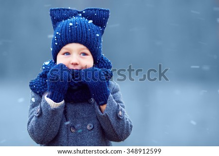 cute little boy, kid in winter clothes walking under the snow - stock photo