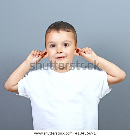 Cute little boy kid making funny face and pulling ears against gray background  - stock photo
