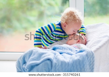 Cute little boy kissing his newborn brother. Toddler kid meeting new born sibling. Infant sleeping in white bouncer under a blanket. Kids playing and bonding. Children with small age difference. - stock photo
