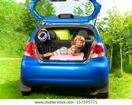 Cute little boy laying on the back of the bags and baggage in the car trunk ready to go on vacation - stock photo