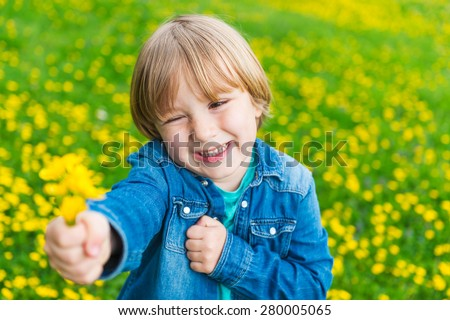 Cute little boy laying with flowers outdoors - stock photo