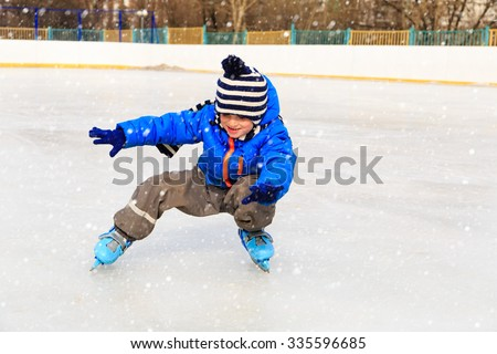 cute little boy learning to skate in winter snow - stock photo