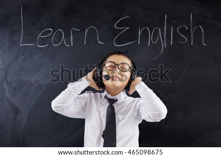 Cute little boy learns English by listening with headphones in the classroom