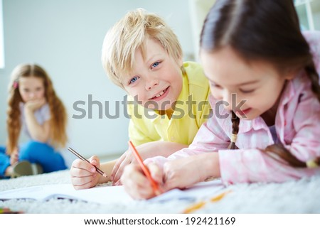 Cute little boy looking at camera while lying on the floor and drawing with his friends near by - stock photo