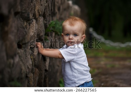 Cute little boy  looking at the camera in outside - stock photo