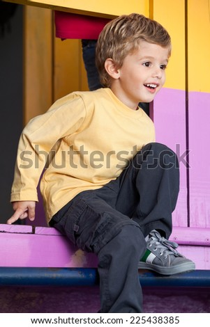 Cute little boy looking away while playing at playhouse - stock photo