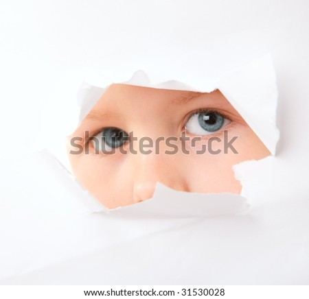 Cute little boy looking through paper hole - stock photo