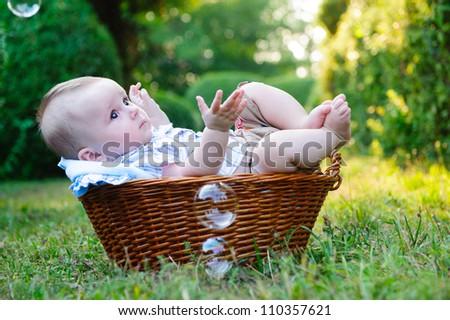 Cute little boy lying in basket in the park - stock photo