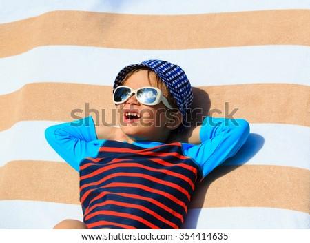 cute little boy lying on a beach towel at summer beach - stock photo