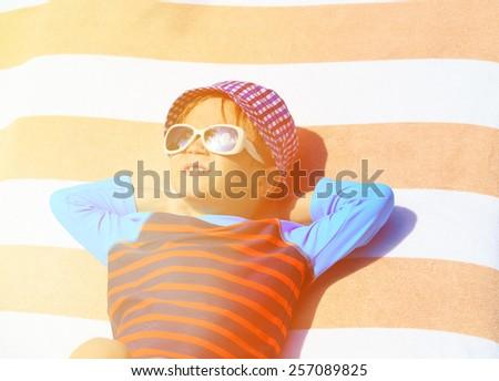 cute little boy lying on a beach towel on summer beach - stock photo