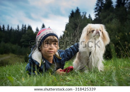 Cute little boy lying on the grass next to his dog. Best friends concept. - stock photo