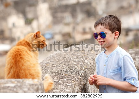 Cute little boy met a cat while walking at typical italian town  during summer holiday vacation - stock photo