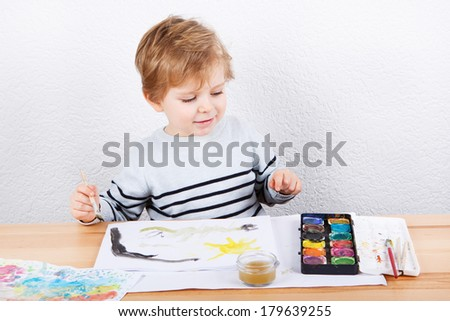 Cute little boy of two years having fun painting at home