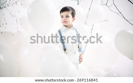 Cute little boy on balloons background - stock photo