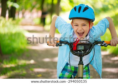 Cute little boy on bike in forest - stock photo
