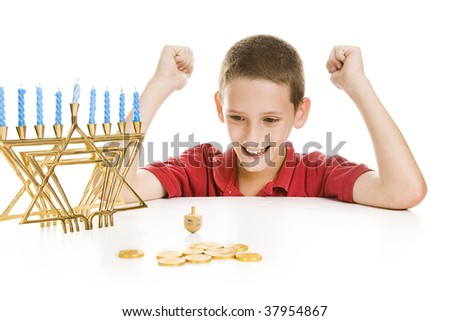 Cute little boy on Chanukah playing with his dreidel.  Isolated on white with menorah and gelt. - stock photo