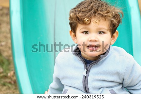 Cute little boy on the slide at the park. - stock photo