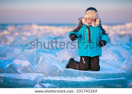 Cute little boy outdoors playing on winter beach on beautiful winter day - stock photo