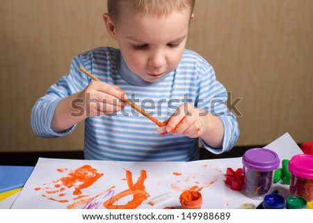 Cute little boy painting at the table