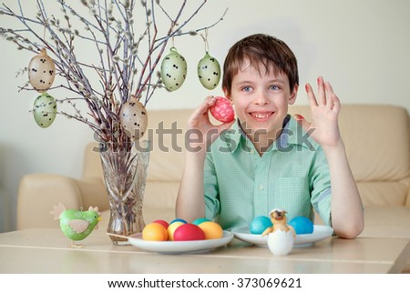 Cute little boy painting colorful Easter egg for hunt indoors - stock photo