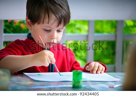 Cute little boy painting with brush - stock photo