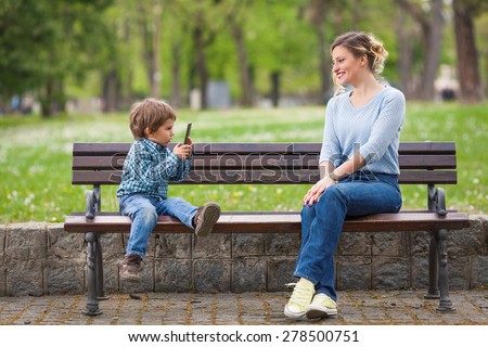 Cute little boy photographing his mother sitting on a park bench - stock photo