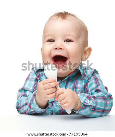 Cute little boy play with a spoon while sitting at table, isolated over white - stock photo