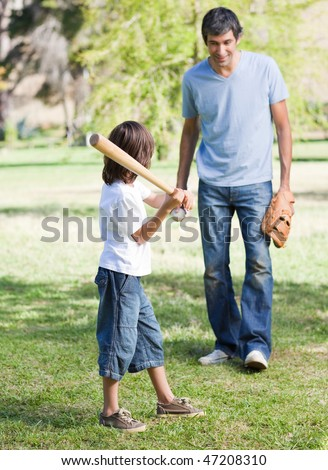 Cute little boy playing baseball with his father in the park - stock photo