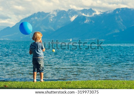 Cute little boy playing by the lake, holding blue baloon - stock photo