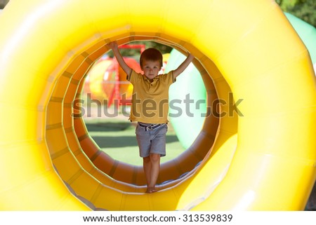 Cute little boy, playing in a rolling plastic cilinder ring, full with air, outdoor - stock photo