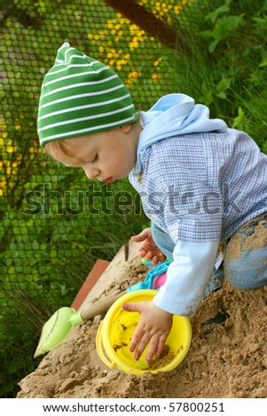 Cute little boy playing in sandbox