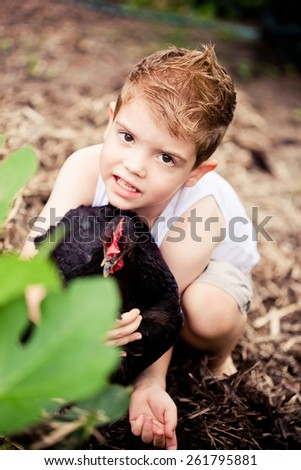 Cute little boy playing in the garden with his bet chicken. - stock photo