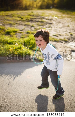 Cute little boy playing jump rope - stock photo