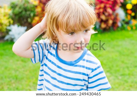 Cute little boy playing outdoors - stock photo