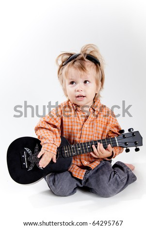 Cute little boy playing ukulele guitar, studio shot - stock photo