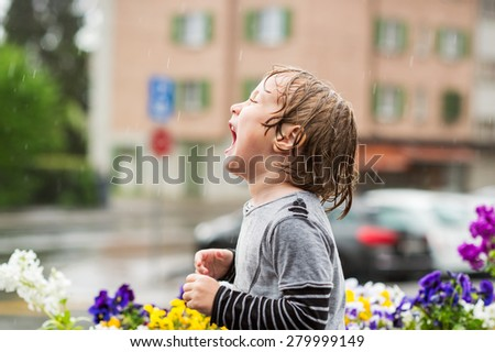 Cute little boy playing under the rain outdoors, catching rain drops by his mouth - stock photo