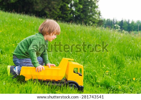 Cute little boy playing with a big yellow toy car outdoors